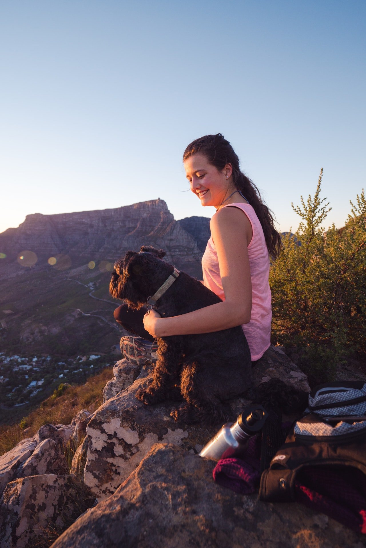 woman with dog on top of mountain